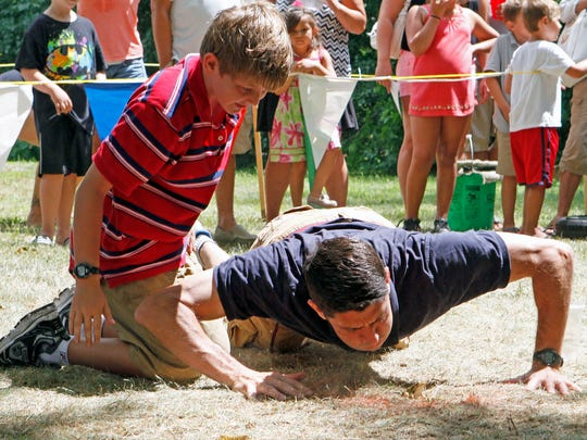 Sam Ryan watches his dad, Congressman Paul Ryan try to get his frog to jump during the frog jumping competition at Duusman Derby Days.