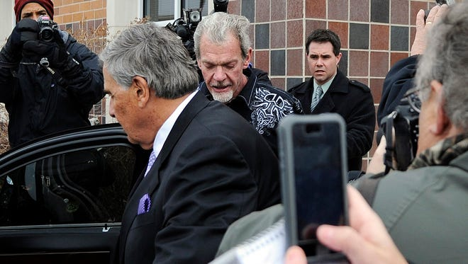 Attorney James Voyles, center left, and Indianapolis Colts owner Jim Irsay, center right, leave the Hamilton County Jail in Indianapolis on Monday. Irsay was released from jail Monday after being held overnight.