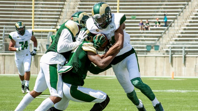 CSU wide receiver Xavier Williams (84) attempts to break away from tacklers Saturday at the spring football game at Hughes Stadium.