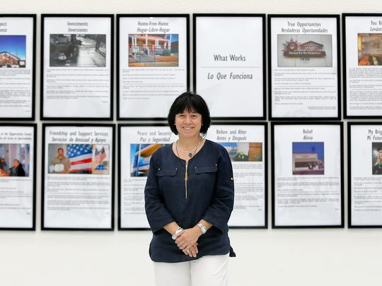 UTEP social work Professor Eva Moya is shown with the Homeless Photovoice, a photo documentary by homeless people in the region, which will be back at UTEP today.