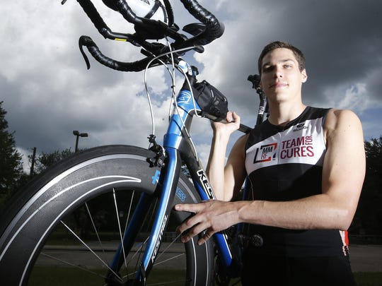 Jason Hohensee holds the bike that he will ride this summer in his first complete Ironman competition, which involves a 2.4-mile swim, 112-mile bike ride and full marathon, a 26.2-mile run.