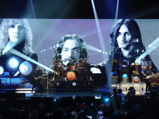 Alex Lifeson, Neil Peart, and Geddy Lee of Rush perform