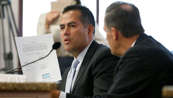 City Manager Tommy Gonzalez holds up one of the documents entered into evidence during his Ethics Review Commission hearing last year. After reading the document, Gonzalez said that he had never seen it and could not reply as to who had generated it.