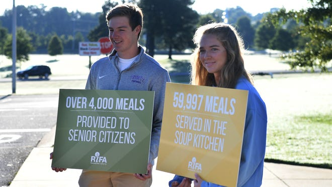 Trinity Christian Academy's Noah Holsigner and University School of Jackson's Kallie Pickens hold up signs during USJ lower school carpool drop-off, Thursday morning, Sept. 7, to remind students to bring canned goods to school. USJ and TCA have teamed up this year to combine their canned-good collections.