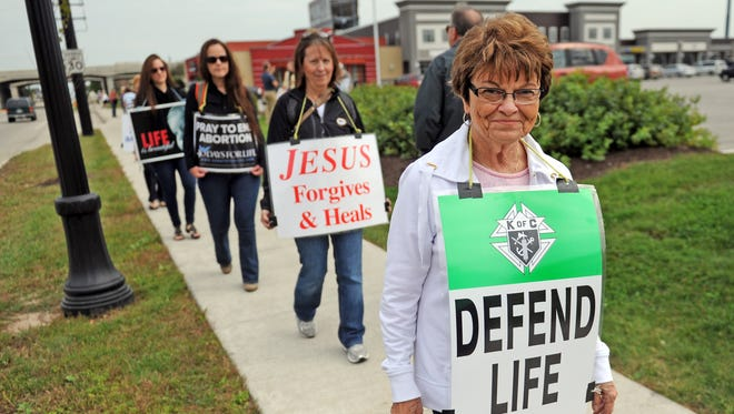 Til Pleba walks along Oneida Street in Ashwaubenon protesting the nearby Planned Parenthood clinic with other members of 40 Days for Life, an anti-abortion group.