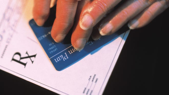Woman's hands with insurance card and prescription slip.