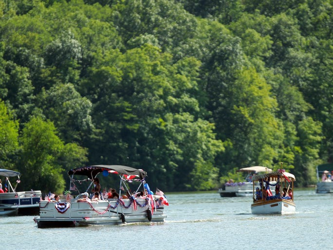 Decorated boats make their way through Lake Macbride during the Fourth of July boat parade.