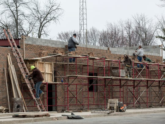Contractors do masonry work Wednesday, March 23, 2016 at the Clay Township Police Department. The  3,170-square-foot expansion is expected to be complete by this summer.