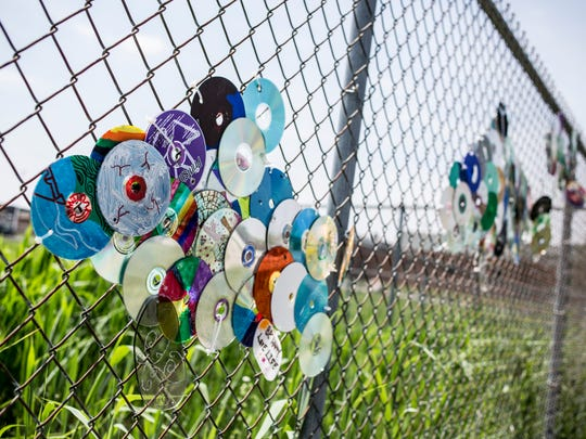 A fence along a sidewalk has been decorated with compact discs arranged to look like fish near Riverview East High School in Marine City. Students in Jason Stier's art class are installing art projects and painting blighted structures along paths frequently used by students as part of a Safe Routes to Schools initiative.