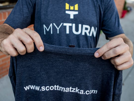 Danny Pink, of Port Huron, shows a My Turn foundation shirt Wednesday, August 17, 2016 in front of Kate's Downtown in Port Huron. Pink's brother, Scott Matzka, was diagnosed with ALS in September of 2015. The My Turn foundation aims to bring awareness to ALS by telling Matzka's story and to raise money to help find a cure for the fatal disease. Kate Voss, owner of Kate's Downtown, will be selling the t-shirts to raise money for My Turn, and is encouraging other city businesses to participate in the ALS Ice Bucket Challenge.