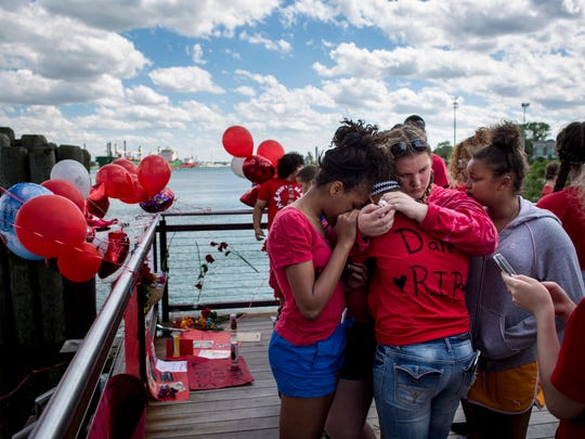 Friends and family hug during a vigil in memory of