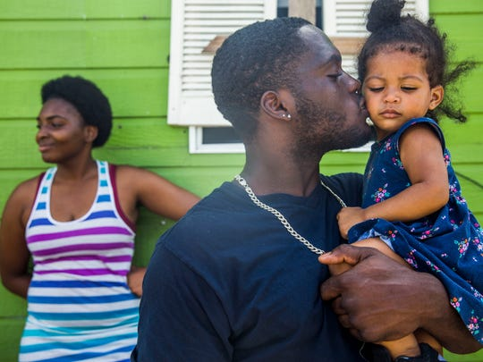 Josh Edison kisses his daughter Kai'ana, 1, as his family cooks the last of their food on their grill at Edison's mother's Immokalee home on Tuesday, Sept. 12, 2017. Edison's mother, Loretha, says she knew she should have stocked up on food and water before the hurricane but she didn't have the money.