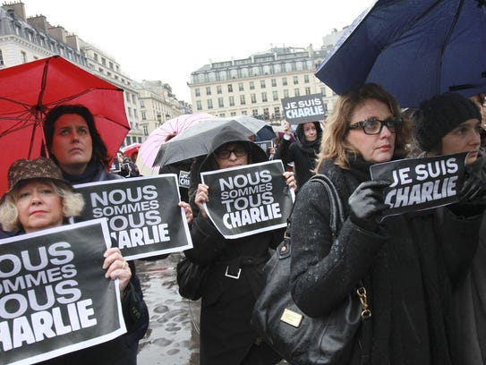 People hold signs in Paris on Jan. 8 as they observe