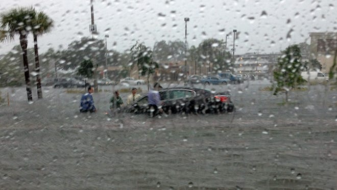 A car is semi-submerged on U.S. 41 in Naples following a flash flood this afternoon.