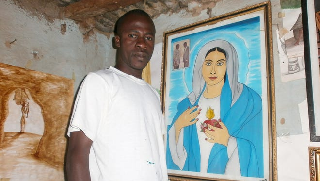 Michel Diarra, who is standing in his house, says he planned to share Christmas with Muslim and Christian friends.