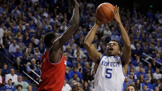 UK guard Andrew Harrison, right, has his shot contested by U of L's Mangok Mathiang on Dec. 28.