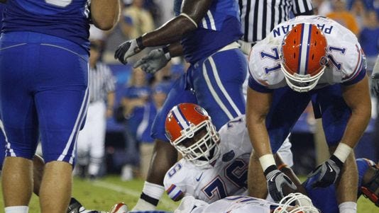 FILE - In this Sept. 26, 2009, file photo, Florida Matt Patchan (71) and Marcus Gilbert (76) look on as Florida quarterback Tim Tebow lies on the turf after being sacked during an NCAA college football game against Kentucky in Lexington, Ky. Tebow received a concussion on the play that put him in the hospital for a night. The parties in a class-action head injury lawsuit against the NCAA that deals with concussion issues announced a settlement in a filing in federal court in Chicago on Tuesday, July 29, 2014.