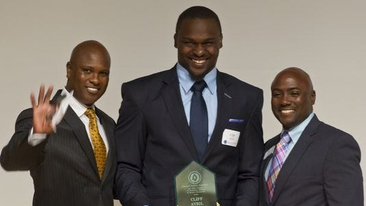 Cliff Avril, center, poses with Purdue football coach Darrell Hazell, left, and Chris Clopton after being awarded the Drew Brees Mental Toughness award on Wednesday.