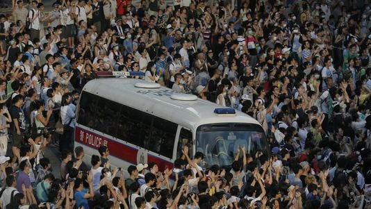 A police car is blocked by thousands of protesters on a main road to the financial central district outside the government headquarters in Hong Kong on Sept. 28.
