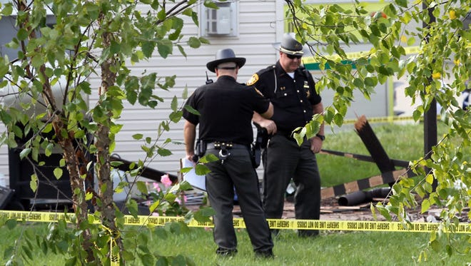 Butler County sheriff's deputies examine wreckage from a small-plane crash on the patio of a house in Liberty Township, Ohio, on Saturday.