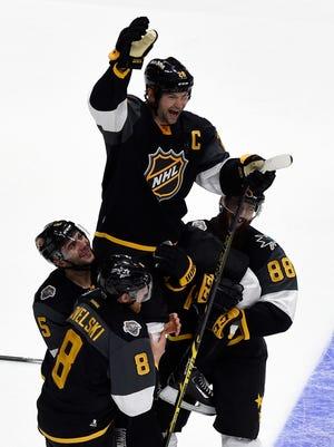 JJoe Pavelski (8) of the San Jose Sharks, Mark Giordano (5) of the Calgary Flames and Brent Burns (88) of the San Jose Sharks hoist John Scott (28) after the 2016 Honda NHL All-Star Final Game.