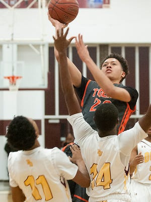 Fern Creek guard-forward Chance Moore puts up a shot but not without colliding with Doss guard-forward Jaylon Hall, bottom left, and Doss forward Terez Traynor, bottom right.02 December 2016