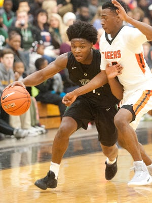Trinity guard Damon McClain turns the corner as Fern Creek guard Anthony Wales keeps on the pressure.10 December 2016