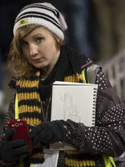 Heidi Schickel, a recent graduate in the UI School of Art and Art History, sketches from the sidelines of Kinnick Stadium during Iowa football games.
