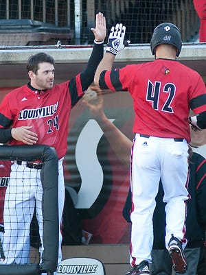 Louisville's Colby Fitch is congratulated by Louisville centerfielder Logan Taylor after Fitch scores on a bases-loaded walk in the bottom of the 3rd inning.03 March 2017