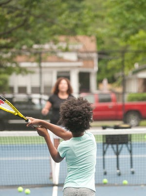 Volunteer tennis coach Sonya Harwood watches as 5th grader Destiny Campbell, age 10 returns the ball Harwood tossed to her. Harwood's tennis program teaches 5th-8th graders in the California neighborhood tennis skills, physical fitness and community service.