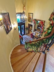 A winding wood staircase trimmed on lighted garland rises from the front foyer