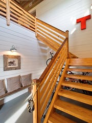 The homeowner/builder's hand crafted stairway from the first floor wood walled foyer opens up to the 2nd floor living spaces.