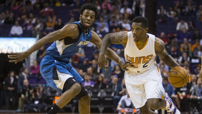 Suns' Eric Bledsoe drives by Timberwolves' Andrew Wiggins at Talking Stick Resort Arena on Dec. 13, 2015 in Phoenix, Ariz.
