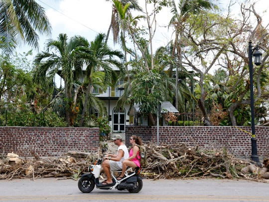A couple rides past the entrance to the Ernest Hemingway Home & Museum in Key West on Sept. 21, 2017.