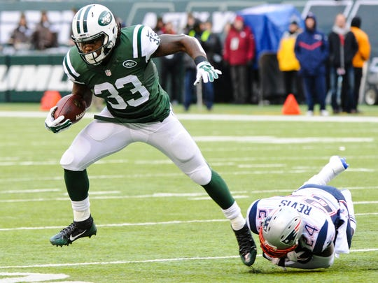 Jets running back Chris Ivory breaks a tackle by New England's Darrelle Revis in the first half Sunday.