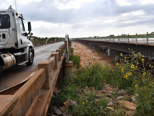 A north-bound truck uses the State Highway 79 bridge built in 1939 that crosses the Red River into Oklahoma. A temporary signal will reduce traffic to one lane at a time while the new bridge is tied into the highway.