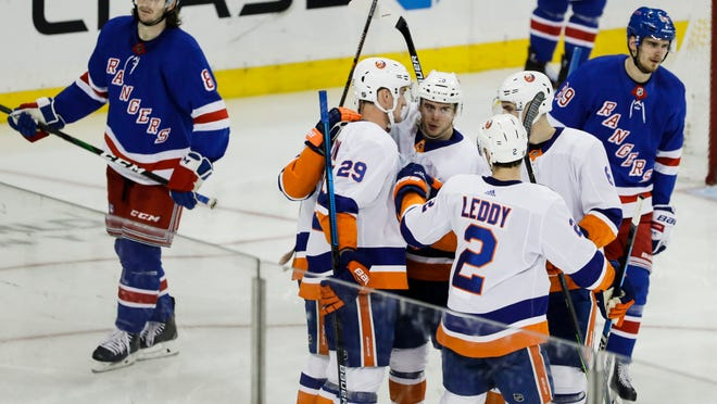 New York Islanders' Brock Nelson (29) celebrates with teammates after scoring a goal as New York Rangers' Jacob Trouba (8) and Pavel Buchnevich (89) react during the third period of an NHL hockey game Tuesday, Jan. 21, 2020, in New York. The Islanders won 4-2. (AP Photo/Frank Franklin II)