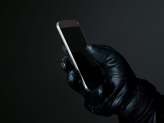 Mobile and cyber security thread concept. Criminal holding smartphone with black leather gloves in darkness. Hacker touching smart phone screen.