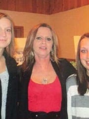 Suzette Langlois, center, stands with her daughters