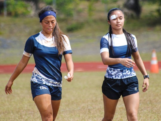 A couple of battle-hardened Academy of Our Lady of Guam Cougars walk to the sideline during a game intermission yesterday during IIAAG High School Girls Rugby opening weekend action Saturday, Jan. 27 at Okkodo High School.