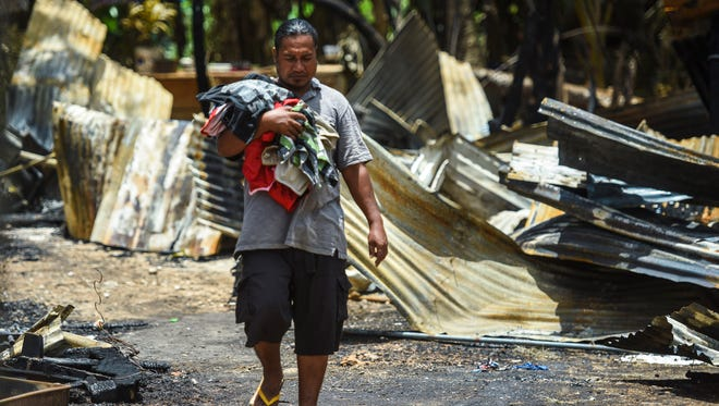 House fire victim Avery Sos emerges from the charred and crumpled remains of what once was a home for him and about 30 others in Dededo on April 19, 2018. A fire broke out within the wood and tin structure the previous day that left the group, consisting of about six families, who find themselves homeless and now living under a 20-foot by 40-foot canopy nearby until a suitable shelter could be found.