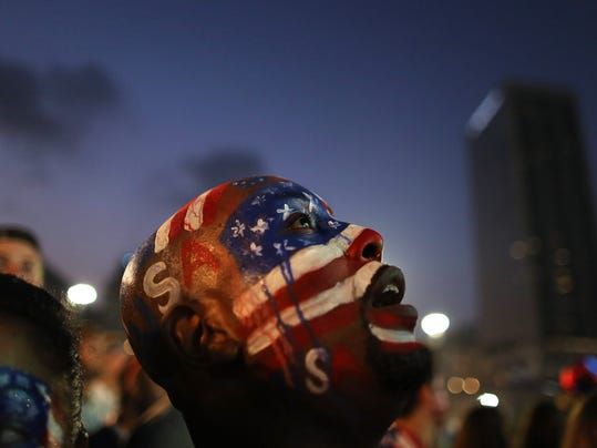 A U.S. soccer fan watches his team's World Cup round of 16 match against Belgium on a live telecast inside the FIFA Fan Fest area on Copacabana beach in Rio de Janeiro, Brazil, Tuesday, July 1, 2014. (AP Photo/Leo Correa)