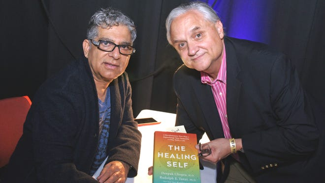 Left to right:  Deepak Chopra signing a book for a guest