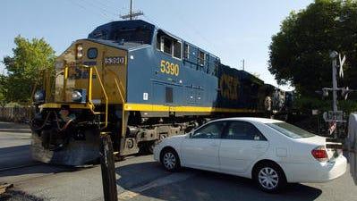 A CSX train rides through a stop in Delaware.