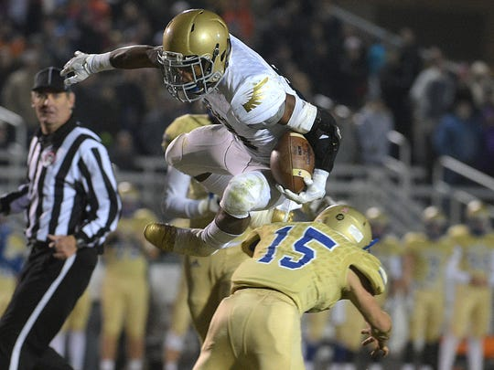 Independence running back Troy Henderson (21) leaps over Brentwood Caleb Mcdaniel (15). Henderson is the Eagles' leading rusher.