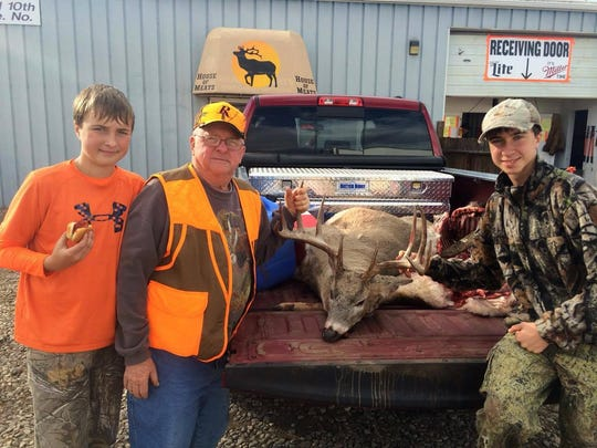 Paul Senn celebrates their kill with his grandsons, Trenton Olson, left, and Teagan Olsen, right, in front of House of Meats last fall.