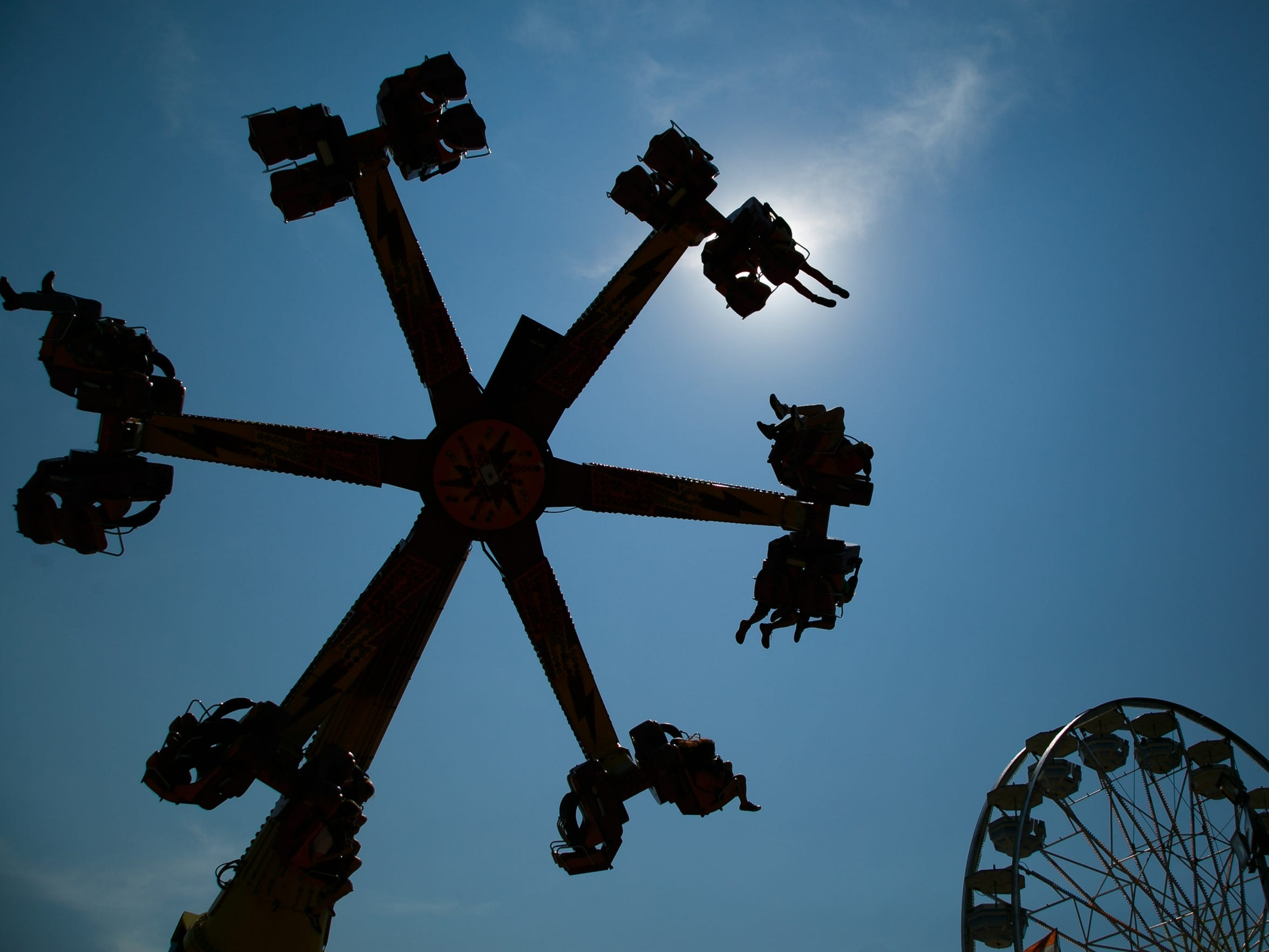 Fairgoers take a spin on rides at the Midway at the Iowa State Fair.
