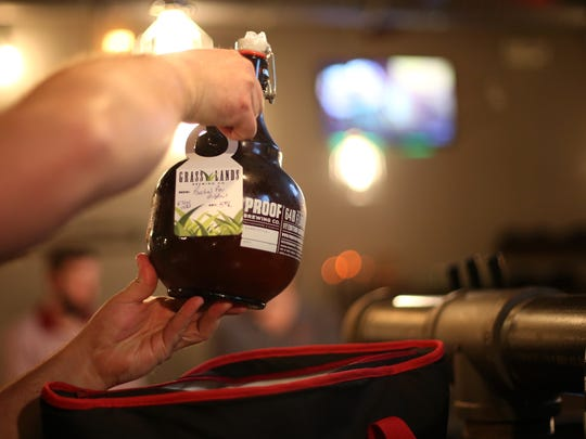 A 64-oz. growler of Grasslands beer is taken home at the Gaines Street brewery .
