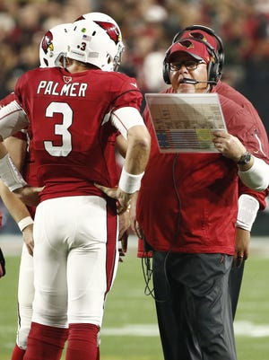 Arizona Cardinals' Carson Palmer and Bruce Arians talk during a timeout against the Green Bay Packers during the NFC Divisional Playoffs on Jan. 16, 2016 in Glendale, Ariz.