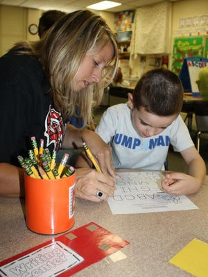 Oakdale Elementary School teacher Heather Packer, left, instructs a kindergarten student during a previous summer program offered by the Oak Hills Local School District.